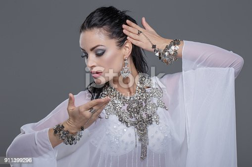 Beautiful oriental belly daner dancing on grey background, portrait