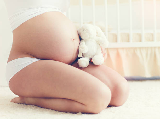 beautiful belly of pregnant young woman sitting on carpet in nursery room stock photo