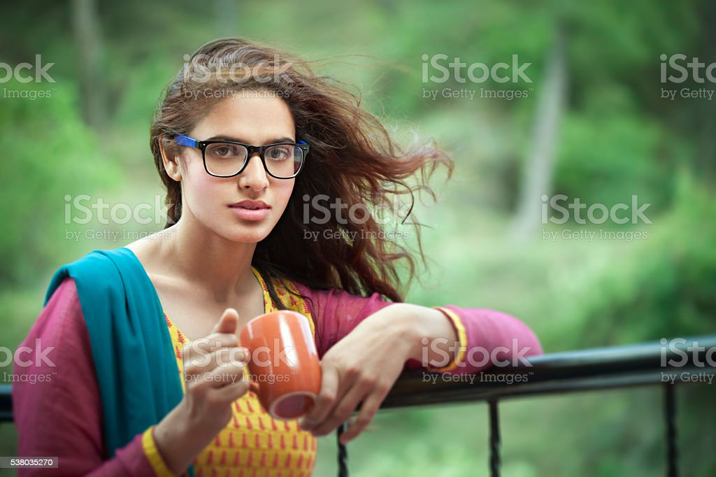 Beautiful bespectacled Asian woman with coffee mug in fresh air. stock photo