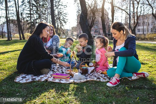 Cheerful and relaxed mothers having a picnic out in the park.