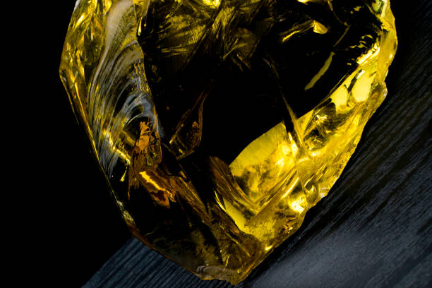 Beautiful big piece of amber heart on a black background. Sun stone. Petrified resin is a natural crystal material for jewelry. Vintage Beautiful big piece of amber heart on a black background. Sun stone. Petrified resin is a natural crystal material for jewelry. Vintage style fossilized pitch stock pictures, royalty-free photos & images