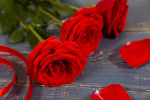 istock Beautiful big red roses with petals and ribbon on wooden background, Valentine's day gift 1284128136