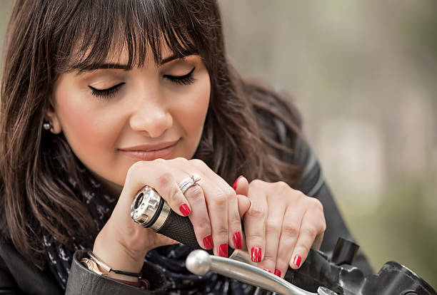 Beautiful biker woman Closeup portrait of beautiful biker woman with closed eyes resting on steering wheel, luxury extreme transport, active lifestyle concept female biker resting stock pictures, royalty-free photos & images