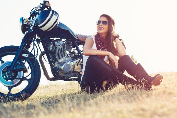 beautiful biker woman sitting by her motorcycle on a highway - biker stock photos and pictures