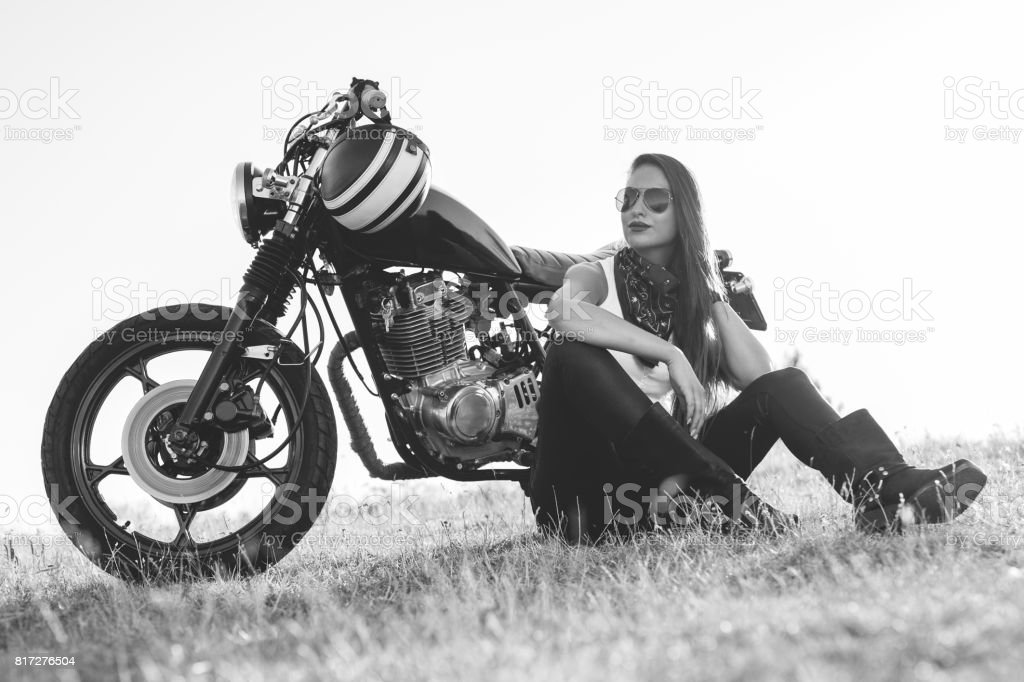 Beautiful biker woman sitting by her motorcycle on a highway stock photo