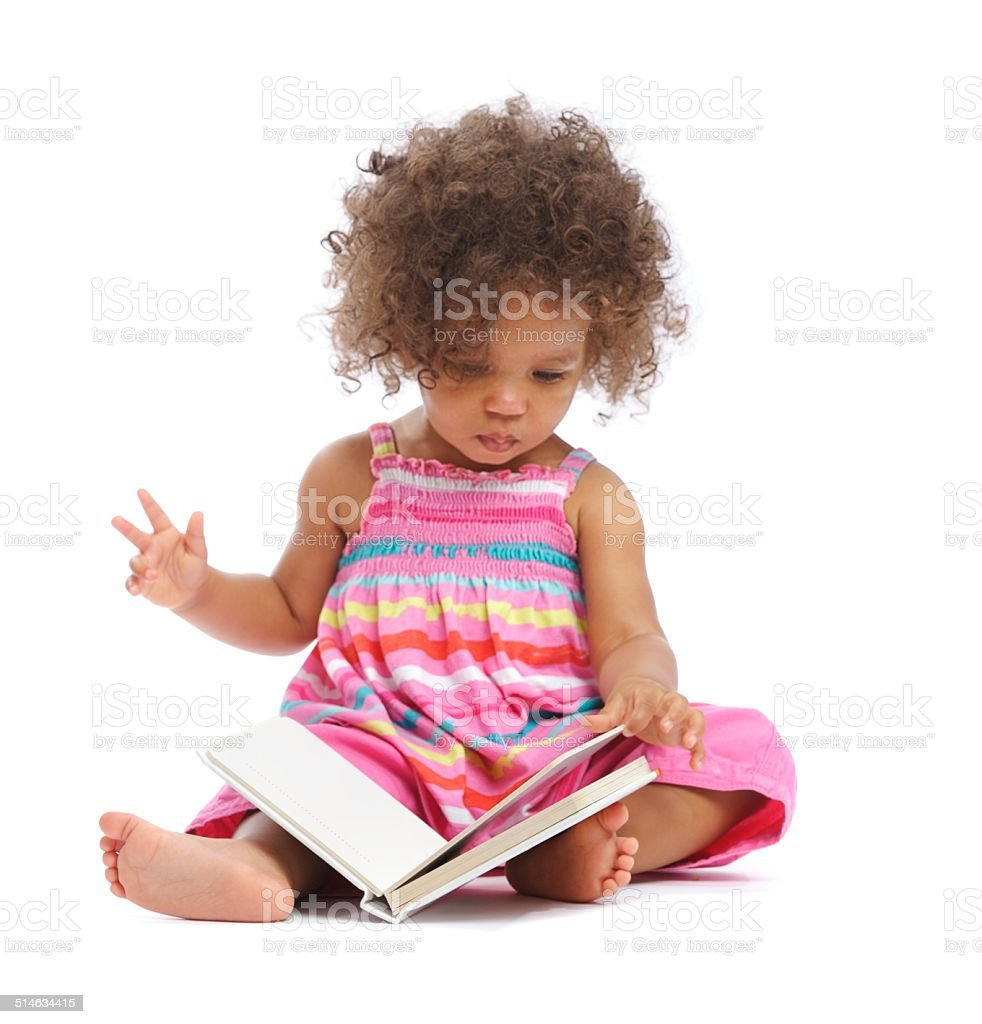 Beautiful Biracial Baby Girl Reading A Book Isolated On White stock photo