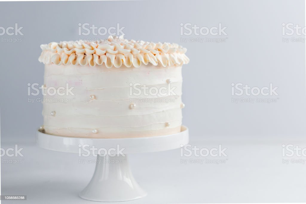Beautiful Birthday Cake decorate with edible pearls on white neutral background. Copy space. Celebration concept. Trendy Layer Cake. Horizontal. stock photo