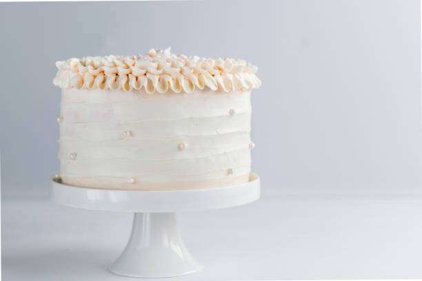 Beautiful Birthday Cake decorate with edible pearls on white neutral background. Copy space. Celebration concept. Trendy Layer Cake. Horizontal. Beautiful Birthday Cake decorate with edible pearls on white neutral background. Copy space. Celebration concept. Trendy Layer Cake. Horizontal. buttercream stock pictures, royalty-free photos & images
