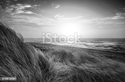 Black and white sunrise landscape image of sand dunes system over beach with wooden boardwalk