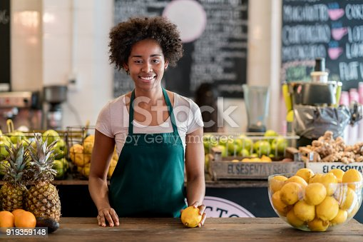 istock Beautiful black business owner of a juice bar stading behind the counter next to delicious raw fruits 919359148