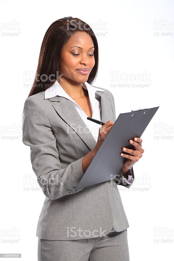 Beautiful black business woman wearing grey suit writing using clipboard stock photo