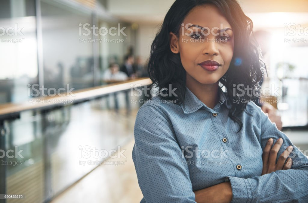 Beautiful black businesswoman with arms crossed in office royalty-free stock photo