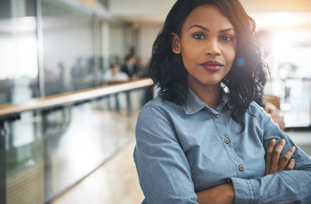 Beautiful black businesswoman with arms crossed in office stock photo
