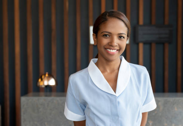 beautiful black chambermaid at the hotel lobby looking at camera smiling - maid stock pictures, royalty-free photos & images