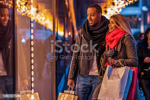 Beautiful black male and female couple enjoying winter shopping in the high street