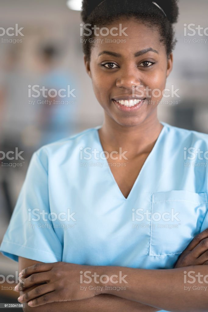 fe76bf15e55 Beautiful black doctor wearing scrubs looking at camera smiling at the  hospital - Stock image .