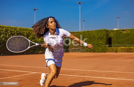 A beautiful young black female tennis player on the court on a beautiful summer day in the sun