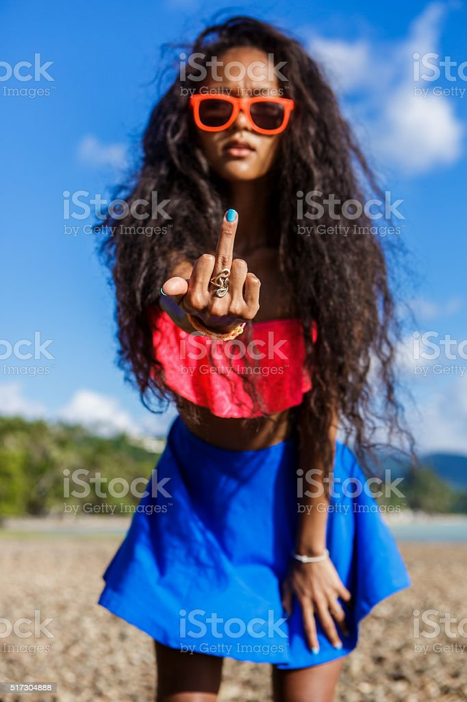 Beautiful black girl in blue skirt on the rock beach. stock photo