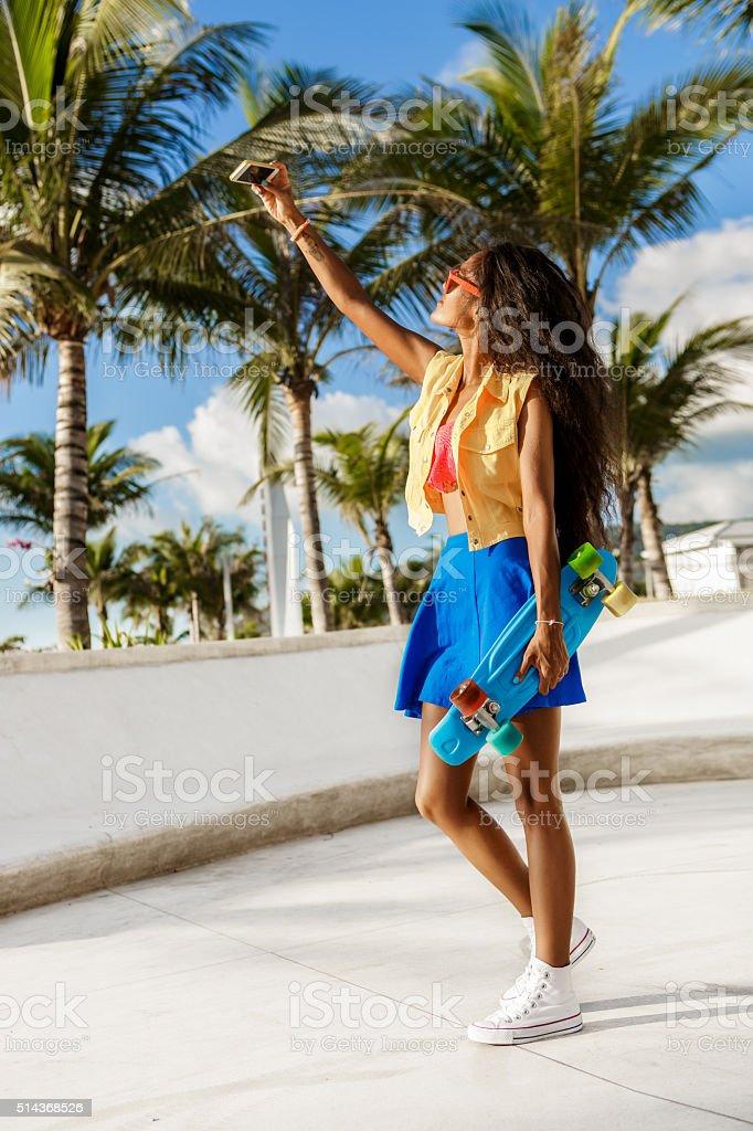 Beautiful black girl in skirt take selfie with her smartphone. stock photo
