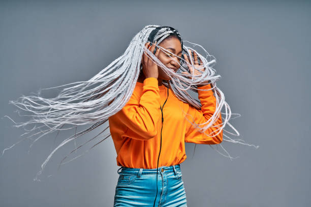 Beautiful black girl listening music. Cheerful young woman with braids making dance moves to the rhythm of music while listening through headphones isolated on gray wall. stock photo