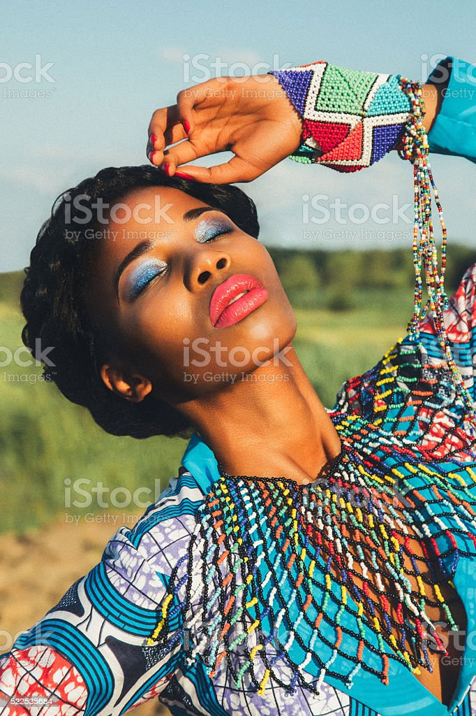 Beautiful black girl model in a blue dress and jewelry stock photo