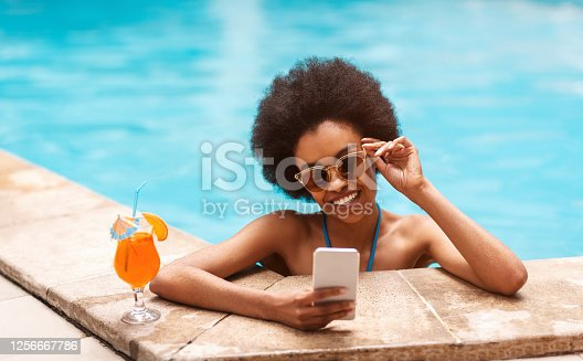 istock Beautiful black girl with tropical cocktail browsing internet on smartphone at swimming pool 1256667786