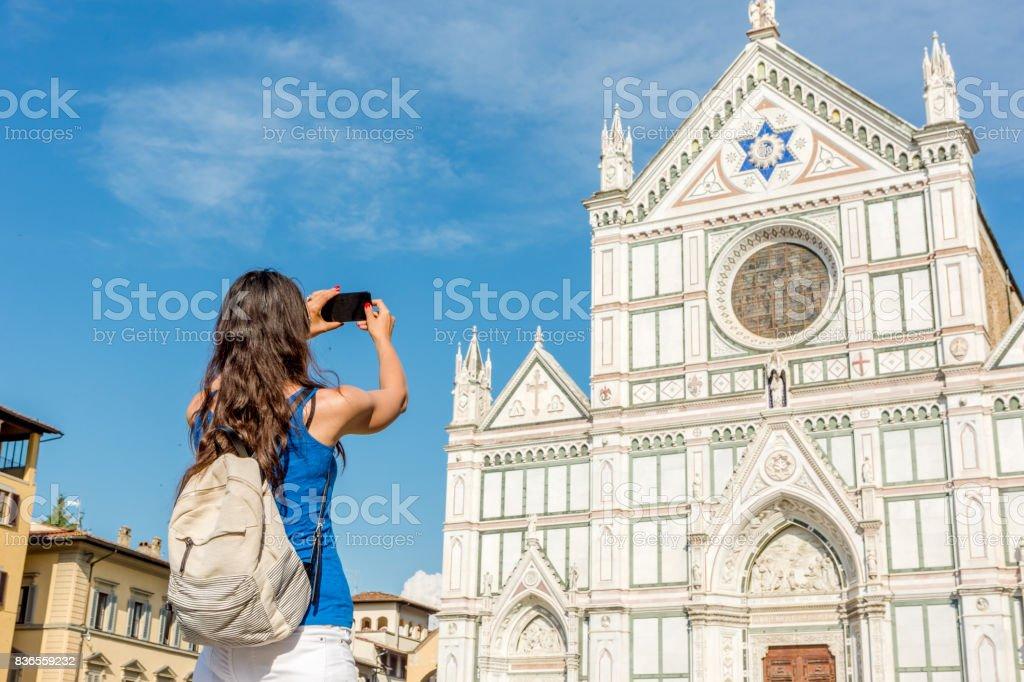 Beautiful, black hair young woman taking photograph of basilica of santa croce - florenceFlorence stock photo
