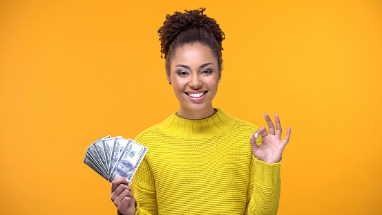 Beautiful black lady showing bunch of dollars and ok gesture, cash-back service