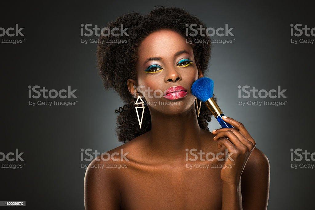 Beautiful black lady with makeup brush stock photo