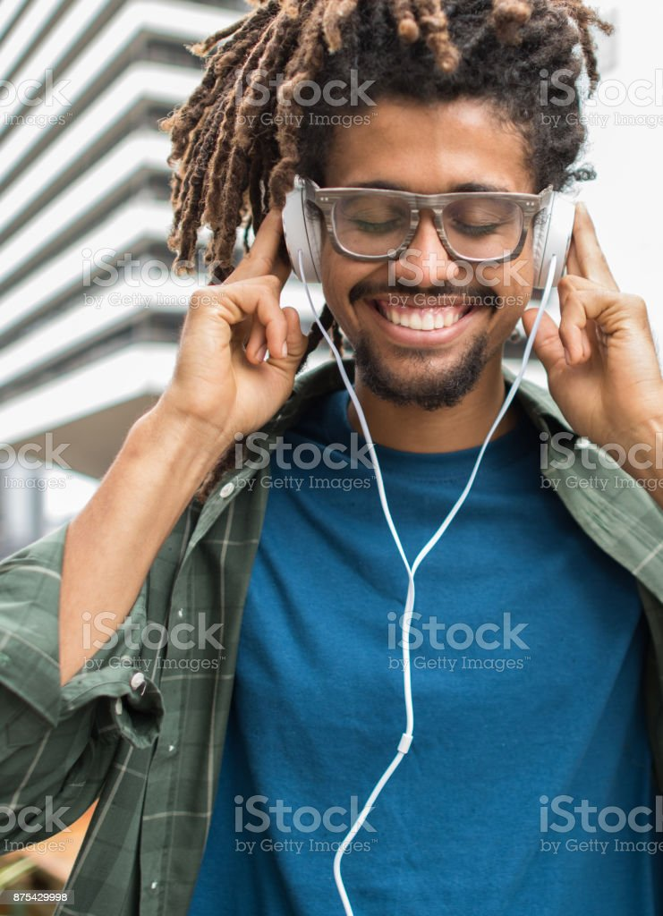 Beautiful black man listening audiobooks in complete enjoyment with headphones smiling stock photo