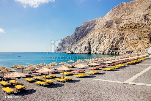 Beautiful black sand beach on Greek island of Santorini in sunny morning. Lot of sun lounge chairs and straw sun umbrellas in a row. Tourist destination concept.