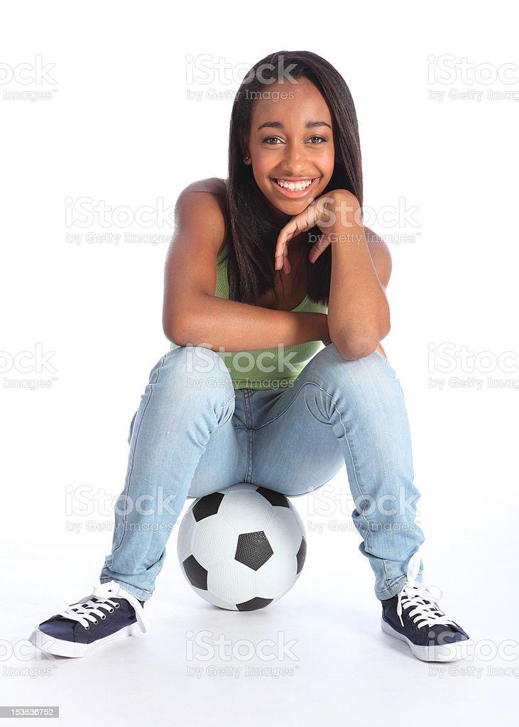 Beautiful black soccer player girl sitting on ball royalty-free stock photo