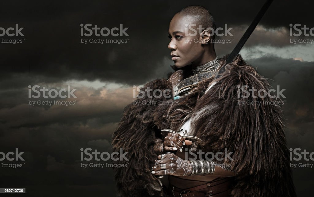 Beautiful black warrior princess holding a sword in studio shot stock photo
