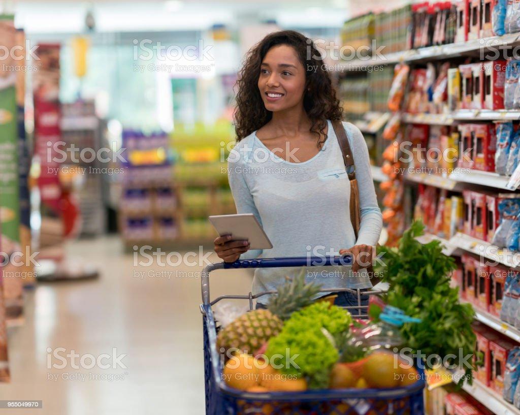 3a4d4bef0 Foto de Linda Mulher Negra No Supermercado À Procura De Mantimentos ...