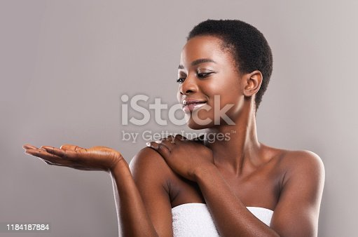 istock Beautiful black woman demonstrating something on her open palm 1184187884