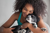 Beautiful black woman hugging her mixed breed dog while she smiles very happy