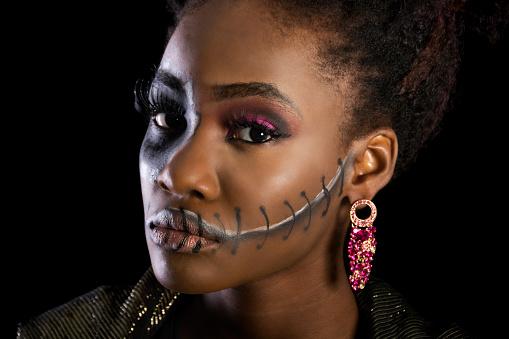 Beautiful black woman in sugarskull makeup, semi-profile.