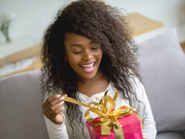 beautiful black woman opening a birthday gift while sitting on the couch at home looking excited - birthday gift stock photos and pictures