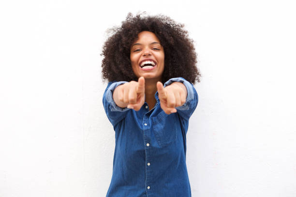 Beautiful black woman pointing fingers and laughing stock photo