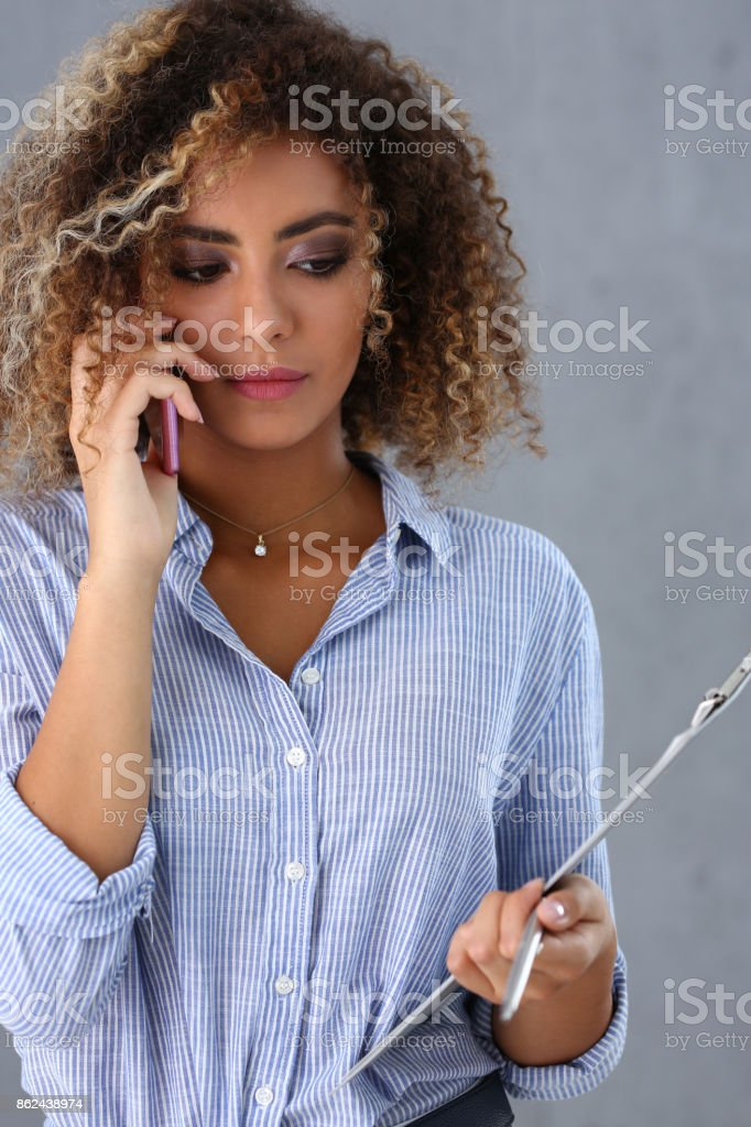 Beautiful black woman portrait. Holds a clipboard and talks stock photo