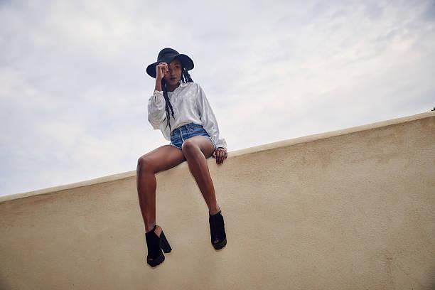 beautiful black woman posing- sitting on a wall - frisuren mit kurzen zöpfen stock-fotos und bilder