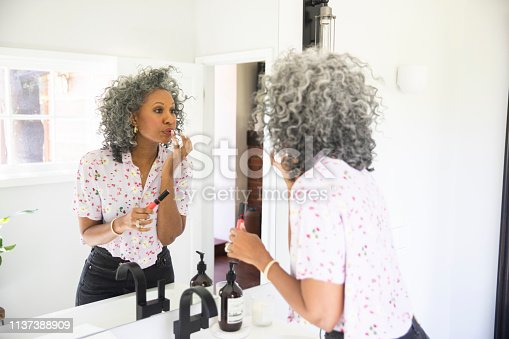 A beautiful black woman puts on her makeup in a bathroom