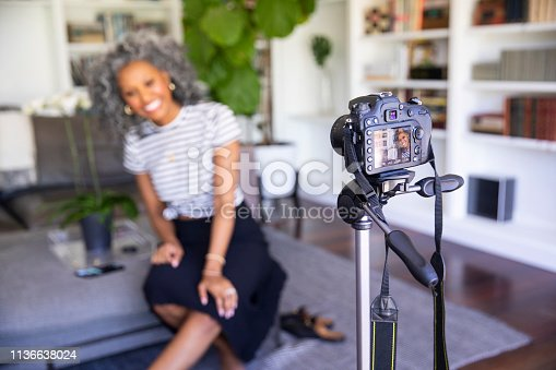 A beautiful black woman with white curly hair  sets up her camera and tripod to record a vlog for her blog