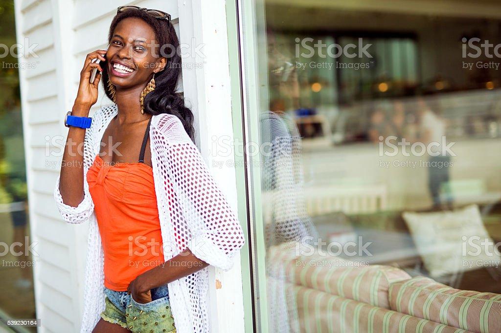 Hermosa mujer negra y sonriente hablando por teléfono foto de stock libre de derechos