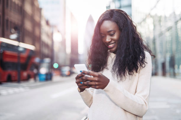 Beautiful black woman using phone in downtown to call crowdsourced taxi stock photo