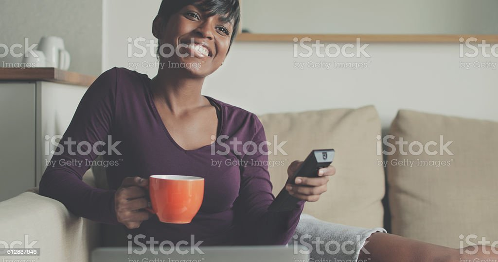 Beautiful black woman watching TV at home stock photo