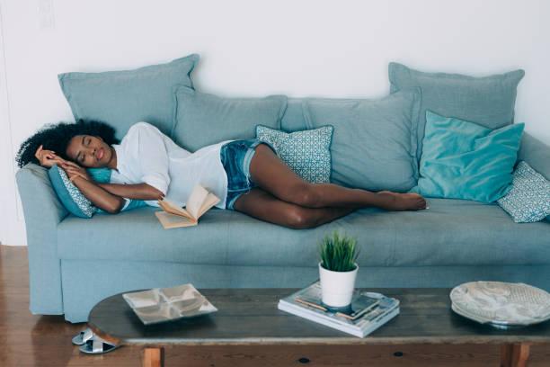 belle jeune femme noire dort dans le canapé - faire un somme photos et images de collection