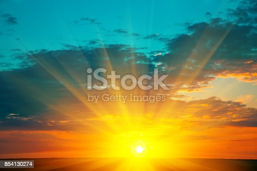 Beautiful blazing sunset landscape at over the meadow and orange sky above it. Amazing summer sunrise as a background.