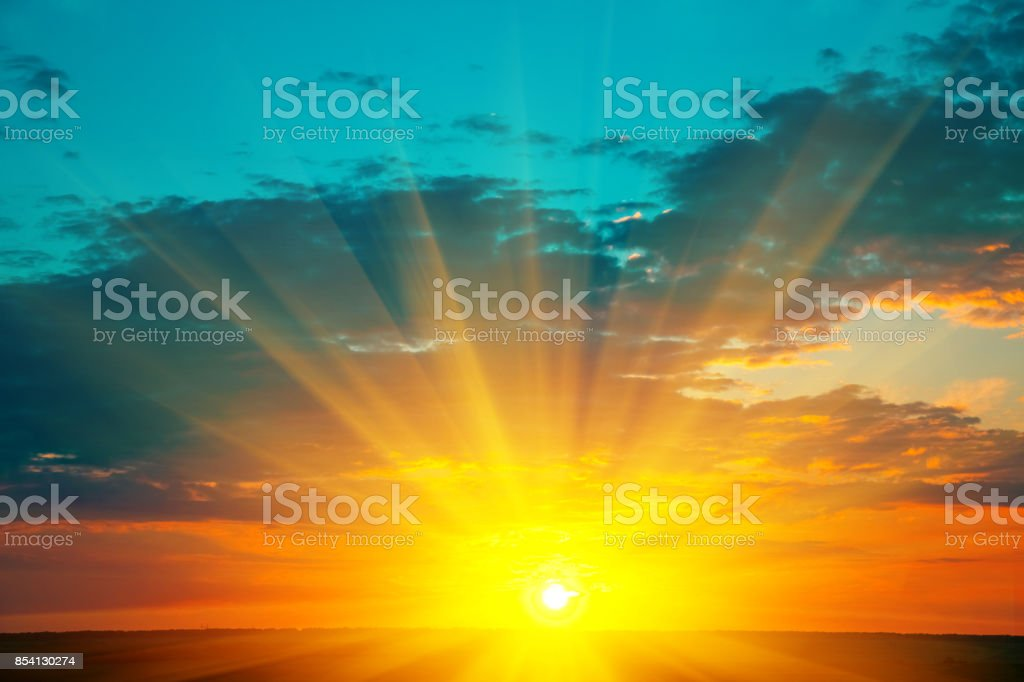 Beautiful blazing sunset landscape at over the meadow and orange sky above it. Amazing summer sunrise as a background. stock photo