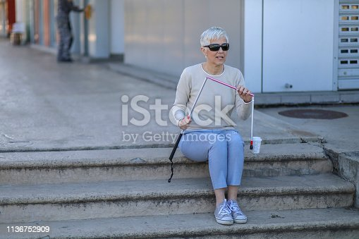 Beautiful blind mature woman n a walk